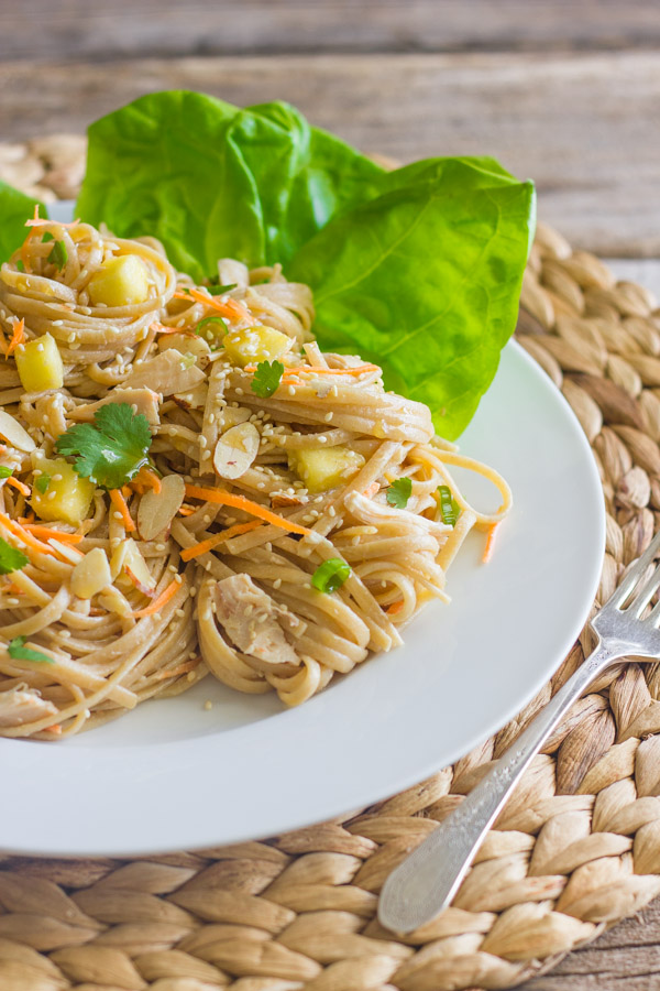 Asian Chicken And Sesame Noodle Salad on a plate with butter lettuce leaves, with a fork next to the plate.
