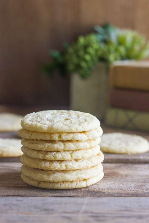 Bakery Style Sugar Cookies in a stack of seven, with more cookies in the background.