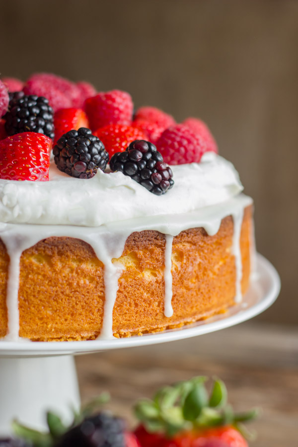 Easy Triple Berry Almond Poke Cake on a cake stand.
