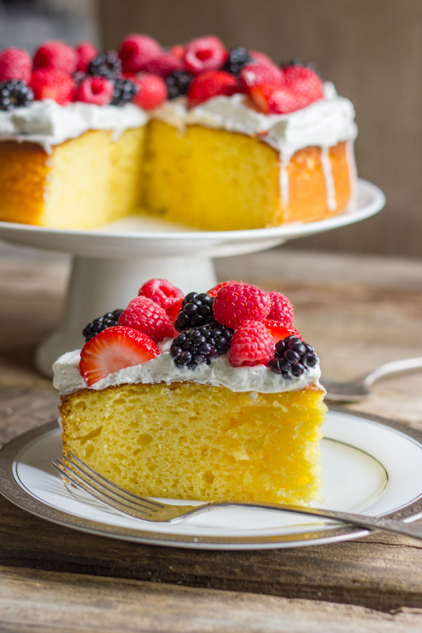 A slice of Easy Triple Berry Almond Poke Cake on a plate with a fork, and the rest of the cake on a cake stand in the background.