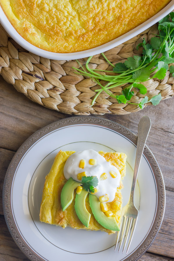 Green Chile Egg Bake Made With Greek Yogurt topped with avocado slices, sour cream, corn kernels and cilantro, on a plate with a fork, sitting next to the baking dish of the egg bake and a bundle of cilantro.