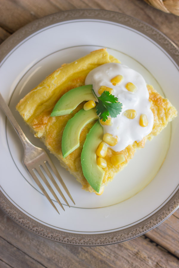 Green Chile Egg Bake Made With Greek Yogurt topped with avocado slices, sour cream, corn kernels and cilantro, on a plate with a fork.
