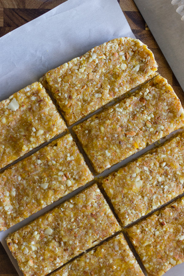 No Bake Apricot Almond Bars on parchment paper on top of a cutting bard with a knife.