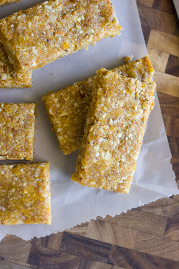 No Bake Apricot Almond Bars on parchment paper on top of a cutting bard.