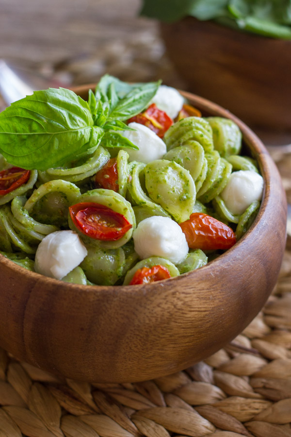 Orecchiette With Pesto and Oven Roasted Tomatoes in a bowl, topped with fresh basil leaves.