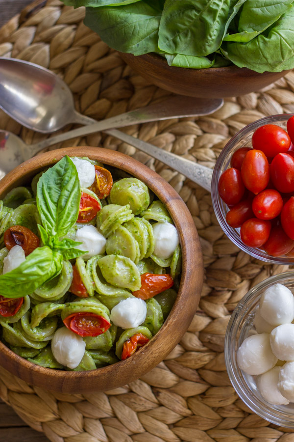 Orecchiette With Pesto and Oven Roasted Tomatoes in a bowl, topped with fresh basil leaves, sitting next to a bowl of fresh mozzarella, a bowl of grape tomatoes, a bowl of fresh basil leaves and two spoons.