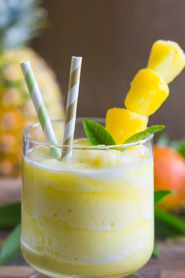 Skinny Pineapple Orange Slush in a glass with two straws and pineapple chunks on a stick.