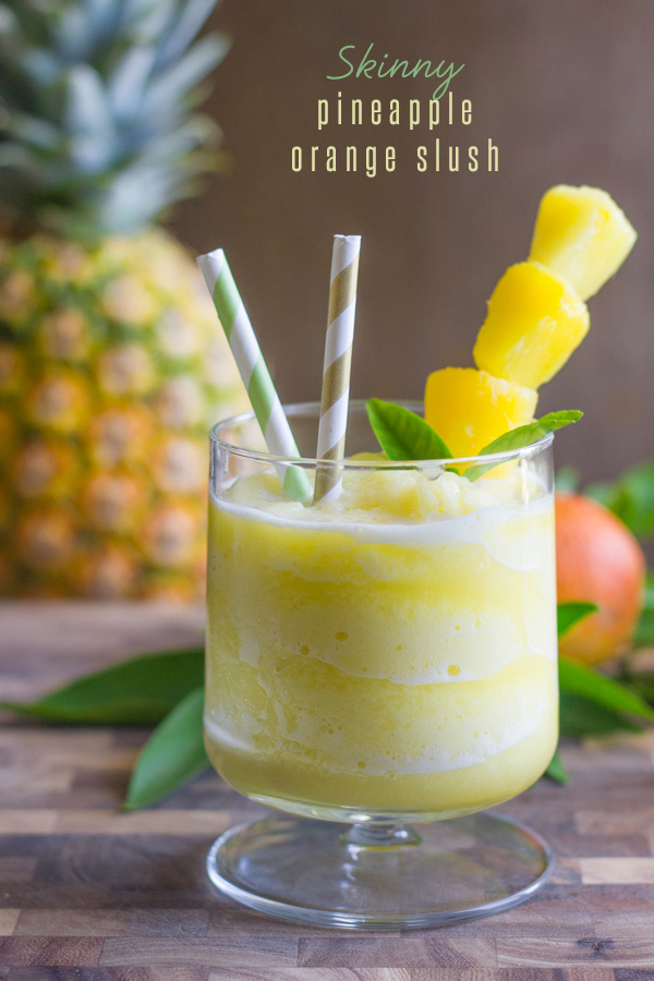 Skinny Pineapple Orange Slush in a glass with two straws and pineapple chunks on a stick, with a whole pineapple in the background.