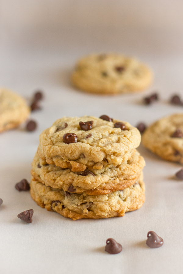 Super Soft Bakery Style Chocolate Chip Cookies stacked in a pile of three, with whole cookies and chocolate chips in the background.