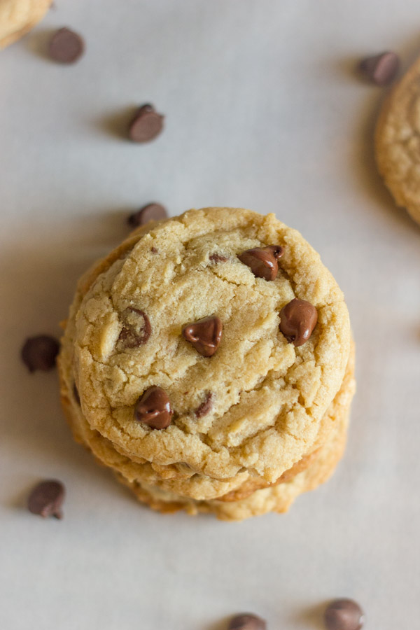 Super Soft Bakery Style Chocolate Chip Cookies in a stack with chocolate chips around it.