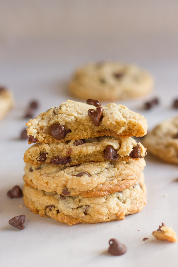 Two Super Soft Bakery Style Chocolate Chip Cookie halves stacked on top of two whole cookies, with chocolate chips and more cookies in the background.