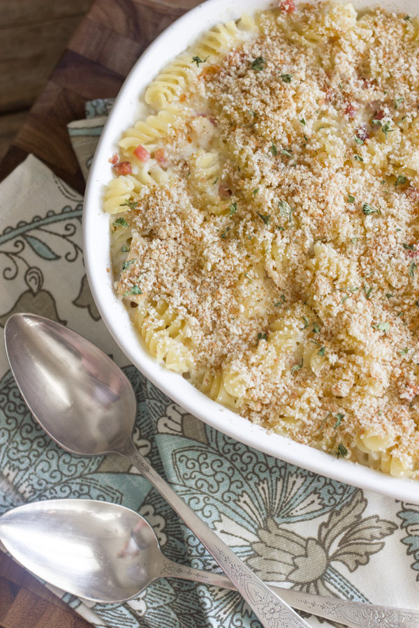 Chicken Cordon Bleu Pasta Bake in a baking dish, with cloth napkins and spoons next to it.