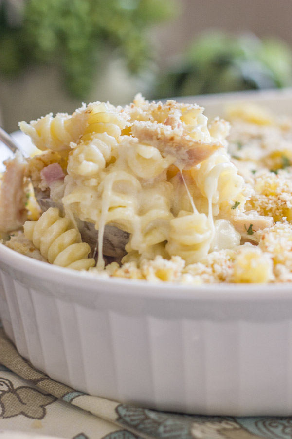Chicken Cordon Bleu Pasta Bake in a baking dish with a serving spoon in it.