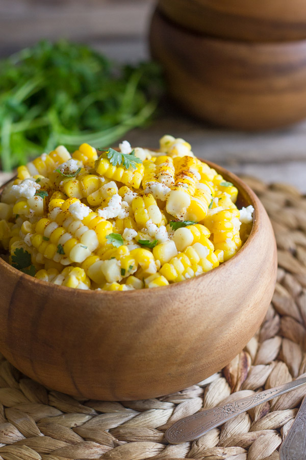 Chili Lime Sweet Corn Salad in a bowl, with a stack of bowls and a bundle of cilantro in the background.