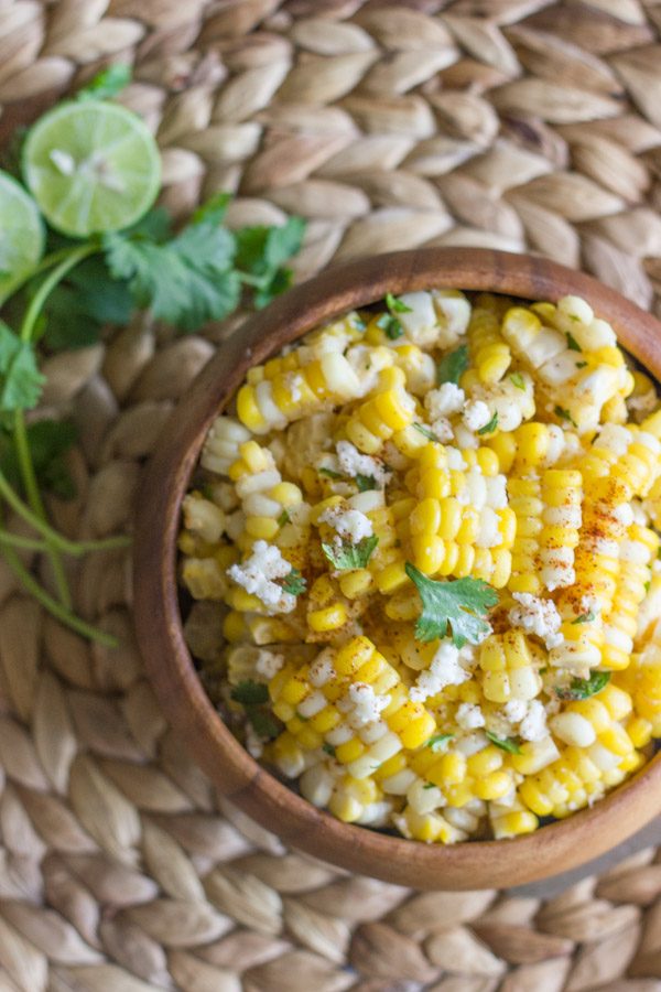 Chili Lime Sweet Corn Salad in a bowl, with a bundle of cilantro and a lime cut in half next to the bowl.
