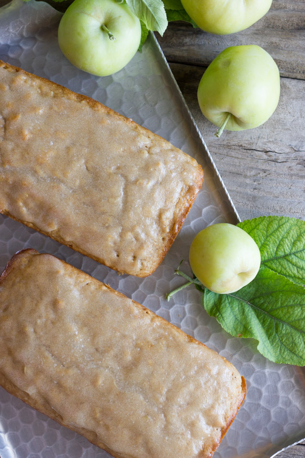 Glazed Apple Cinnamon Oatmeal Bread loaves on a serving platter, with whole apples next to them.