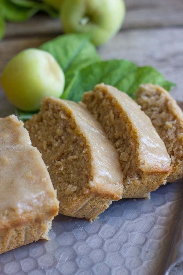 Glazed Apple Cinnamon Oatmeal Bread sliced on a serving platter, with whole apples in the background.