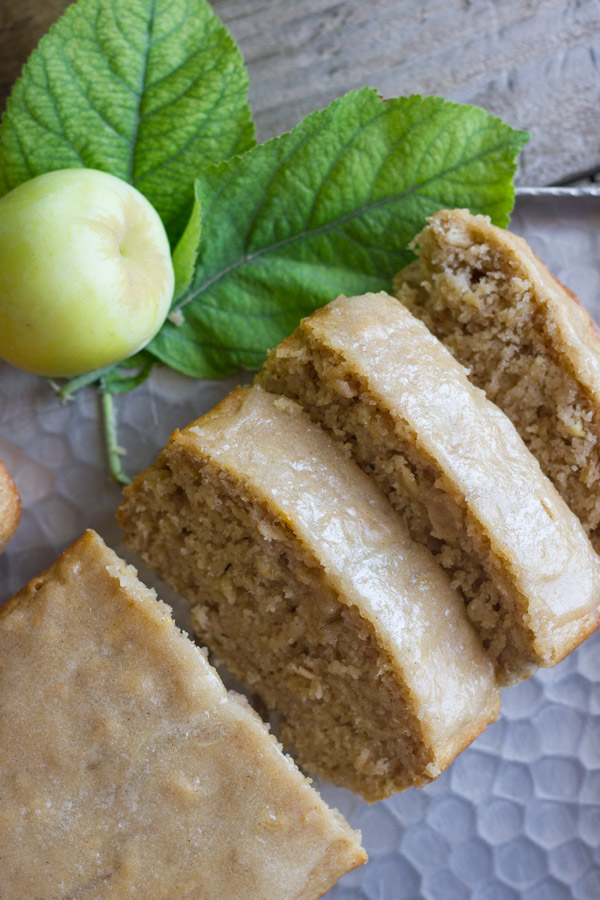 Glazed Apple Cinnamon Oatmeal Bread sliced on a serving platter, with a whole apple and leaves next to it.