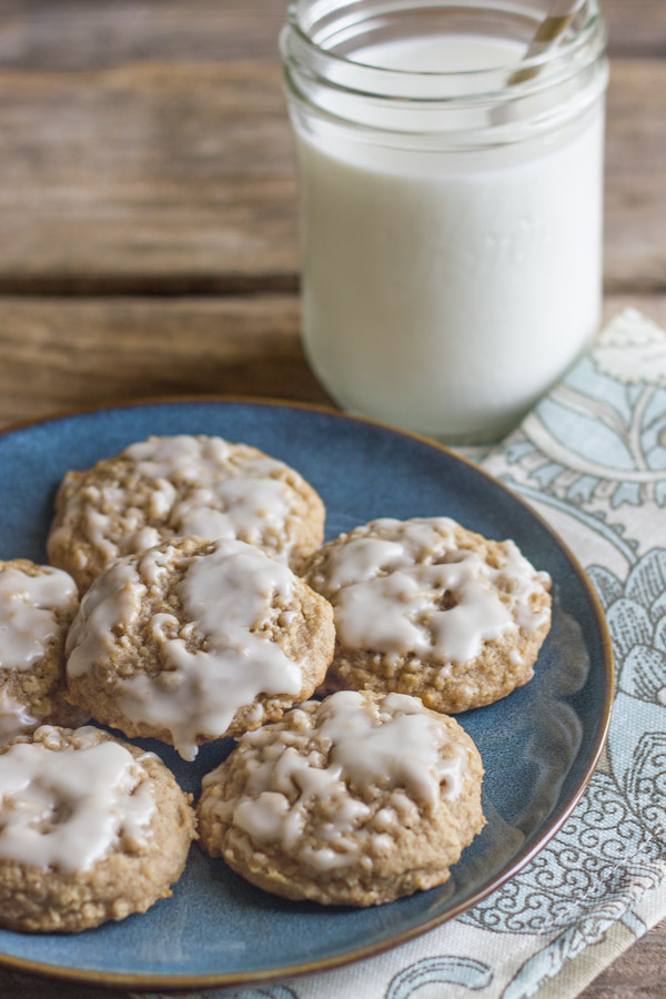 Maple Iced Oatmeal Cookies on a blue plate with a cloth napkin under it and a glass of milk next to it.