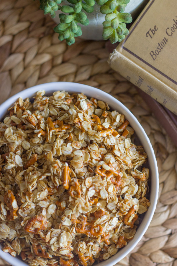 Pretzel Granola Made With Coconut Oil in a bowl, sitting next to a stack of books and a plant.