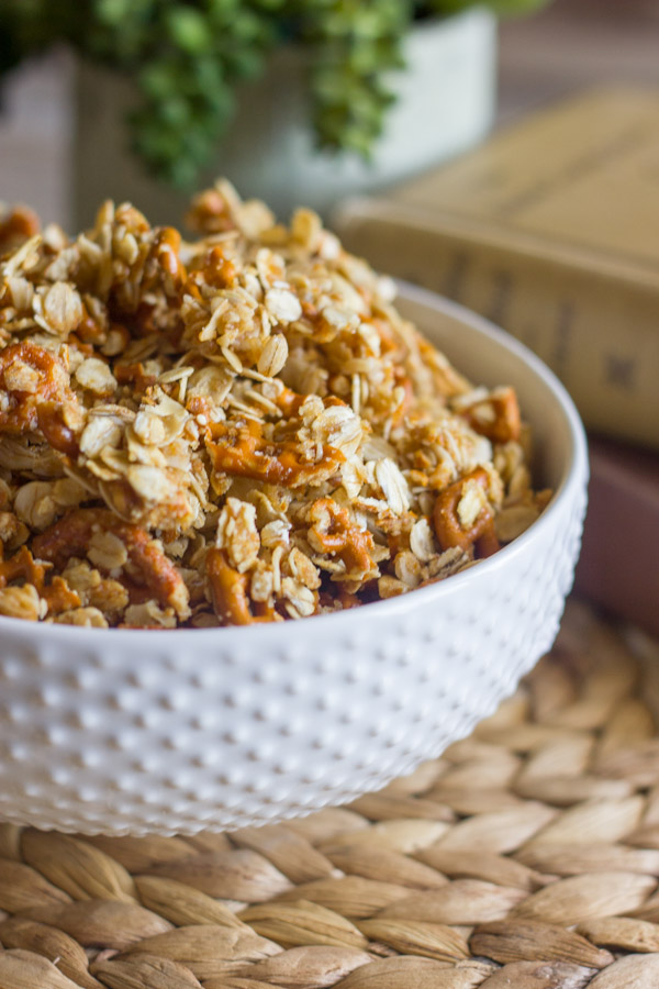 Pretzel Granola Made With Coconut Oil in a bowl, with a stack of books and a plant in the background.