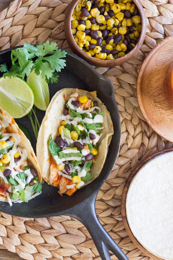BBQ Chicken Tacos arranged in a mini cast iron skillet with some lime wedges and fresh cilantro, sitting next to a small bowl of corn and black beens, and a plate with tortillas on it.