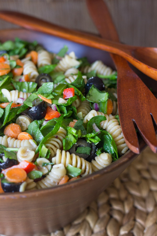 Chopped Spinach and Pasta Salad With Balsamic Vinaigrette in a large wooden bowl, with wooden serving utensils on top.