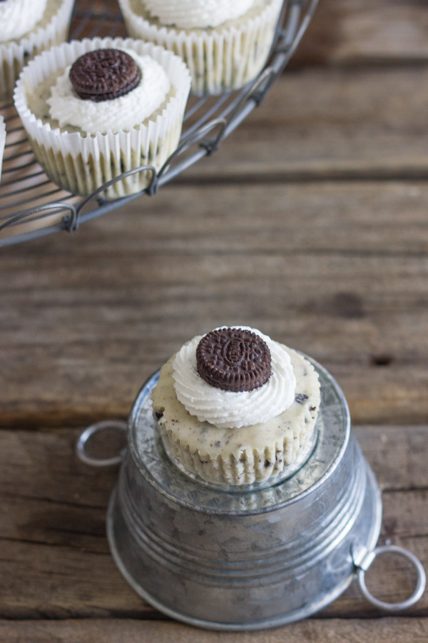 Cookies and Cream Cheesecake Cup sitting on a mini galvanized bucket that is upside down, with more Cookies and Cream Cheesecake Cups arranged on a cake stand next to it.