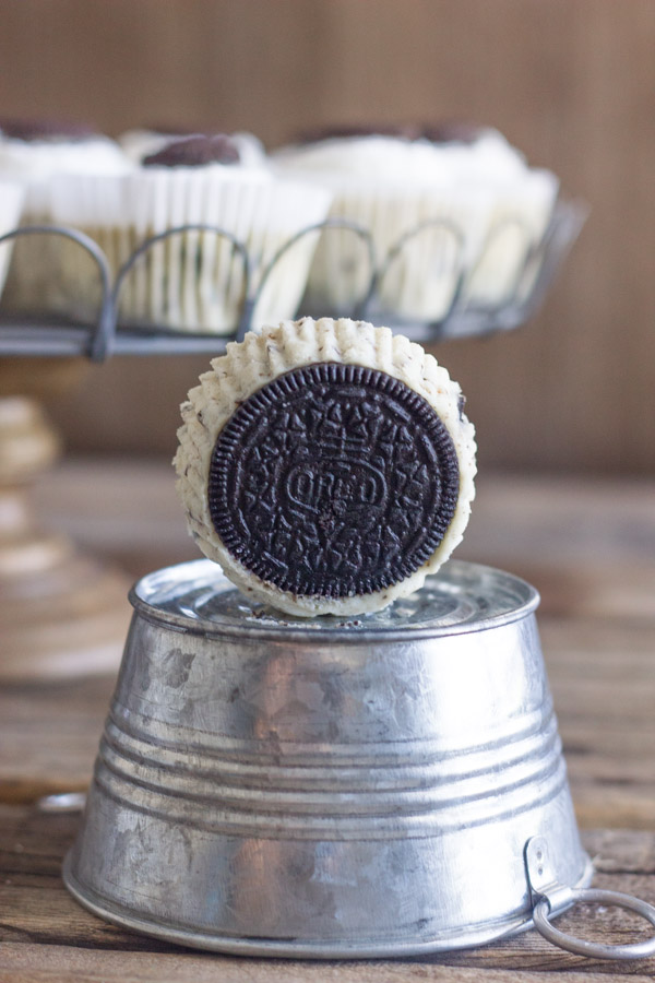 Cookies and Cream Cheesecake Cup sitting on its side showing the Oreo cookie bottom on a mini galvanized bucket that is upside down, with more Cookies and Cream Cheesecake Cups arranged on a cake stand in the background.