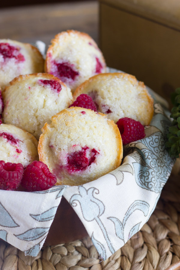Healthier Raspberry Almond Muffins in a cloth lined bowl with a few fresh raspberries.