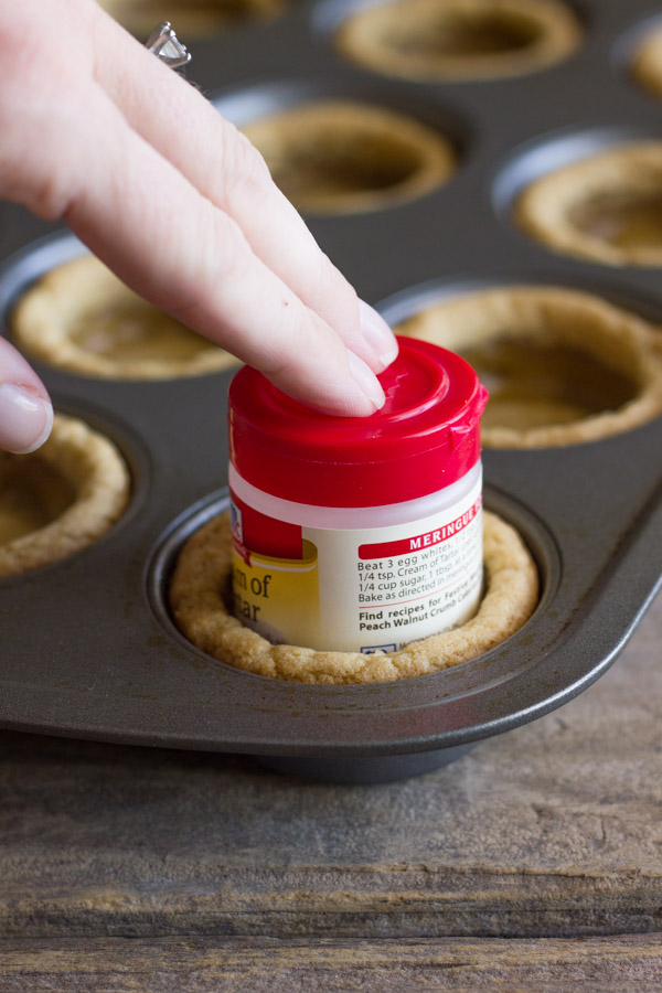A small spice container being used to press down the center of the baked cookie dough to make the little well in the center for the Ice Cream Sundae Cookie Cups.