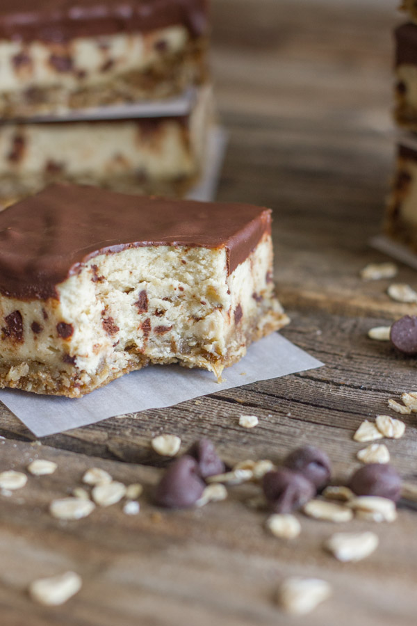 Oatmeal Chocolate Chip Cheesecake Bar with a bite out of it on a board with oats and chocolate chips on it, with more Oatmeal Chocolate Chip Cheesecake Bars stacked in the background.