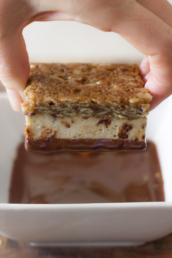 Oatmeal Chocolate Chip Cheesecake Bar being held over a square bowl of melted chocolate.