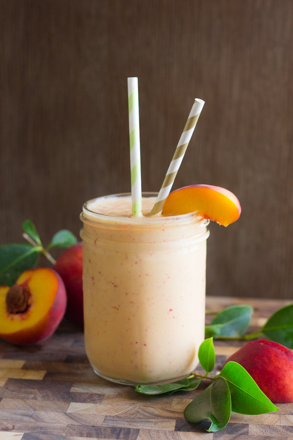 Skinny Peach Cream Slush in a glass with two straws and a peach slice, sitting on a cutting board with peaches in the background.