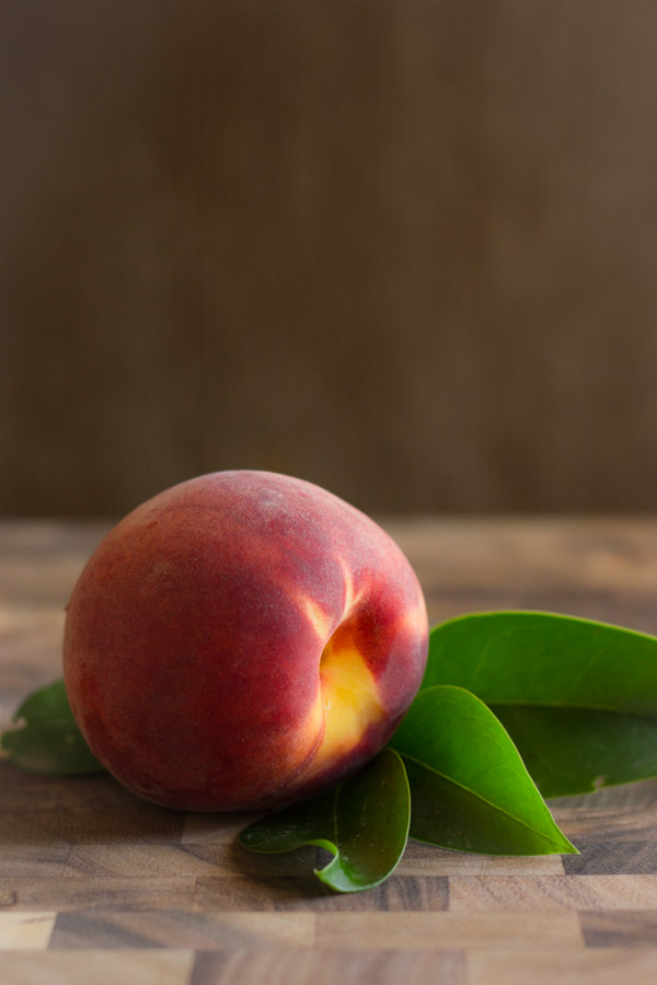 A whole peach on a cutting board.