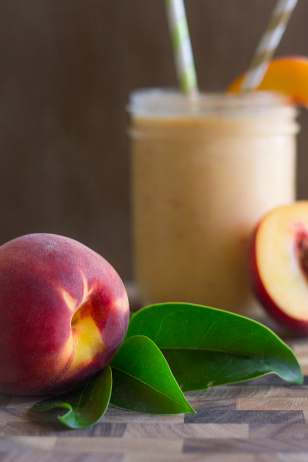 A whole peach on a cutting board, with a Skinny Peach Cream Slush in a glass with two straws and a peach slice in the background.