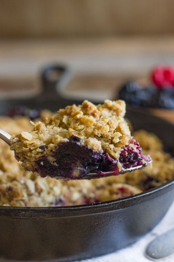 Triple Berry Skillet Crisp on a serving spoon, with the cast iron skillet of Triple Berry Skillet Crisp in the background.