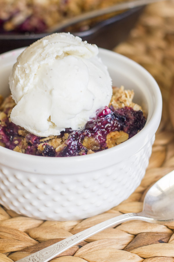 Triple Berry Skillet Crisp in a glass dish with a scoop of vanilla ice cream on top.