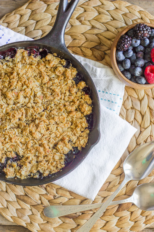 Triple Berry Skillet Crisp in a cast iron skillet, with a bowl of berries and spoons next to it.
