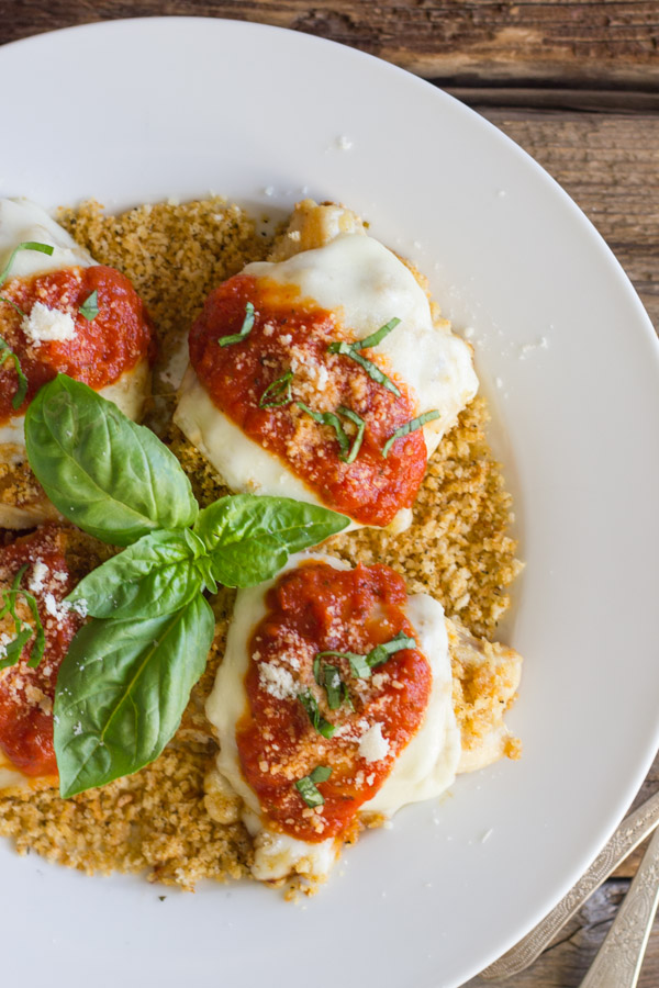 Easy Chicken Parmesan With Toasted Panko on top of a thin layer of the toasted Panko on a serving plate, topped with red sauce, grated Parmesan and some thinly sliced fresh basil, with fresh basil leaves in the center of the serving plate.