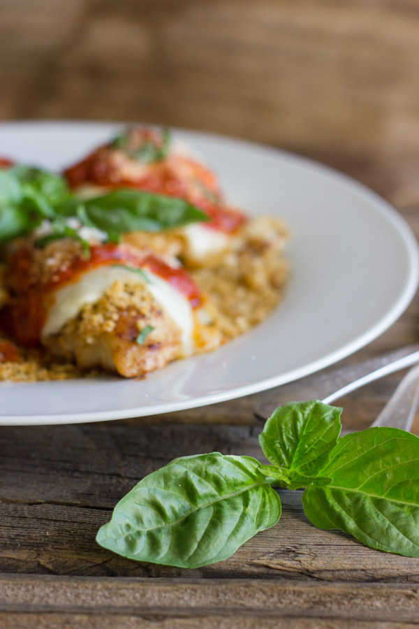 Easy Chicken Parmesan With Toasted Panko on top of a thin layer of the toasted Panko on a serving plate, topped with red sauce, grated Parmesan and some thinly sliced fresh basil, with fresh basil leaves in the center of the serving plate, and more fresh basil leaves next to the plate with some silverwear.