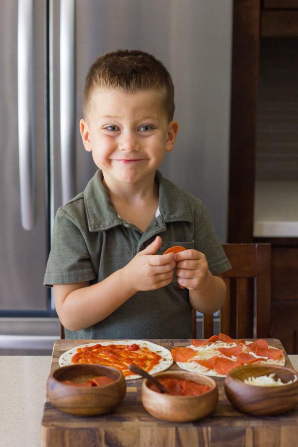 Waffled Pizza Pocket ingredients on a cutting board with a little boy assembling his pizza.
