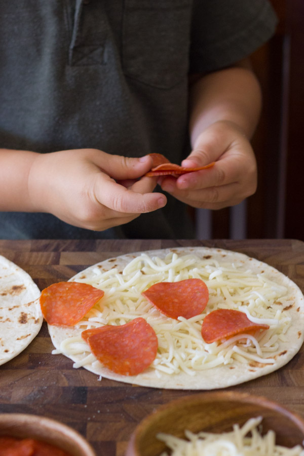 A tortilla with cheese and pepperoni on it, with more pepperoni being placed on it by a child.