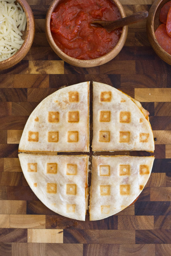 Waffled Pizza Pocket cut in four pieces on at cutting board with a bowl of mozzarella cheese, a bowl of pizza sauce and a bowl of pepperoni next to it.