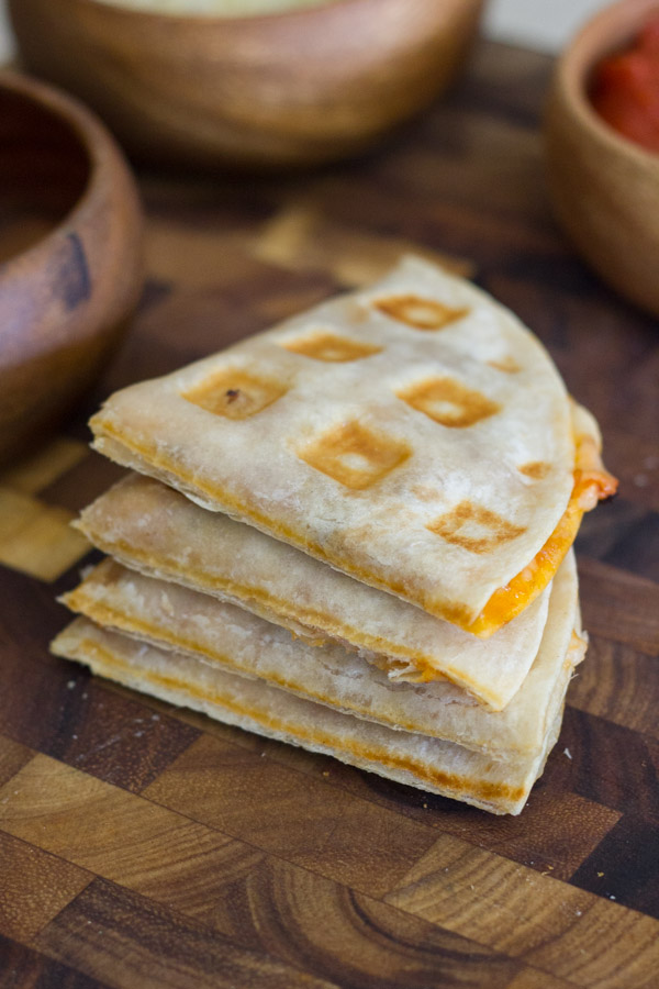 Waffled Pizza Pocket cut in four pieces and stacked in a pile on a cutting board, with bowls of ingredients in the background.