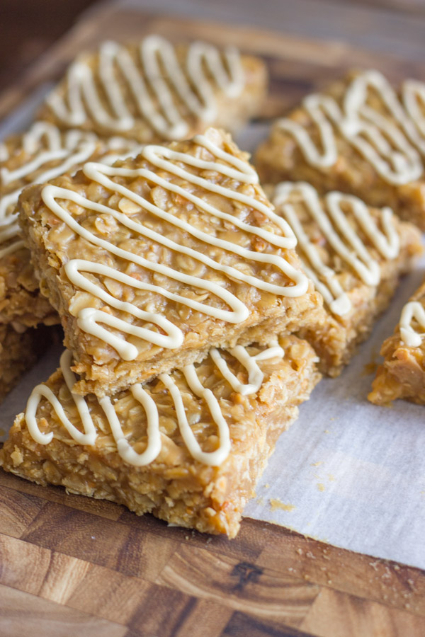 Maple Almond Oat No Bakes cut into squares on parchment paper on a cutting board.