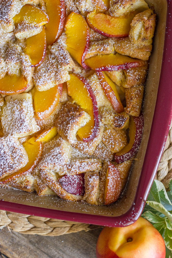 Peaches and Cream French Toast Bake in a baking dish with a whole peach sitting next to it.