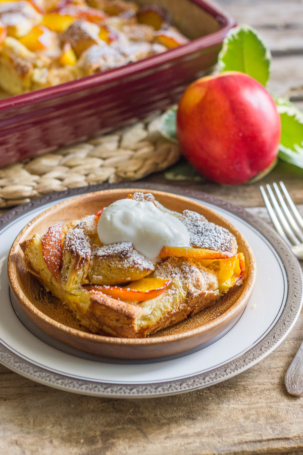 Peaches and Cream French Toast Bake topped homemade whipped cream on a plate, with the baking dish of Peaches and Cream French Toast in the background with a whole peach.