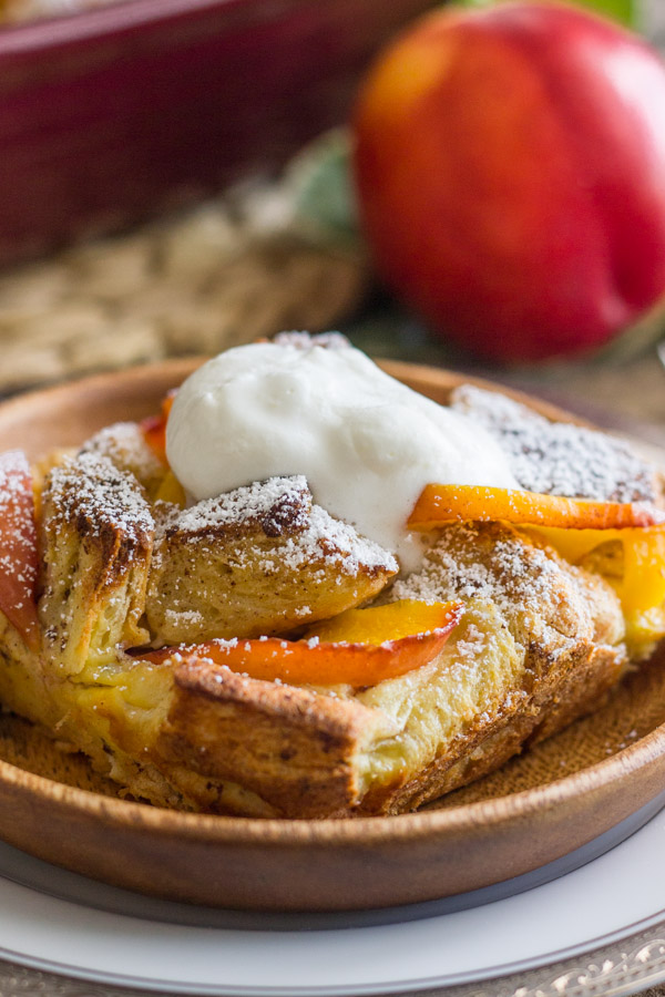 Peaches and Cream French Toast Bake topped with homemade whipped cream on a plate, and a whole peach in the background.