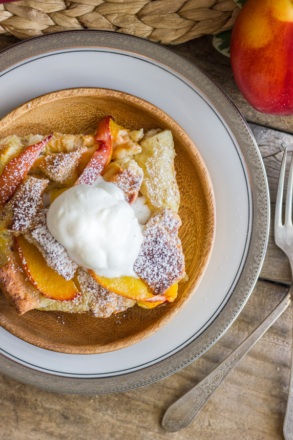 Peaches and Cream French Toast Bake topped with homemade whipped cream on a plate, with a fork and a whole peach next to it.